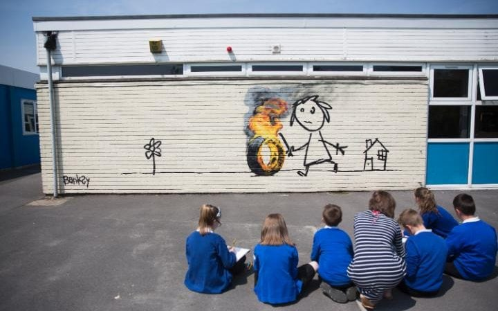Students at the Bridge Farm Primary School in Bristol, gather round a new Banksy mural