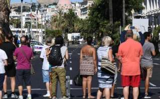People look at a truck stand guarded by the police on the Promenade des Anglais seafront