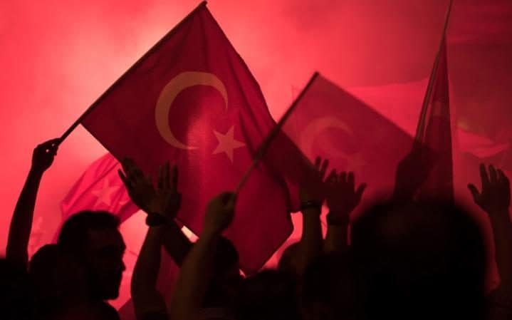 eople shout slogans and hold Turkish national flags during a demonstration, against the failed Army coup attempt