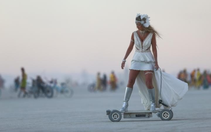 A woman rides an electric scooter during Burning Man at the Black Rock Desert north of Reno, Nevada.