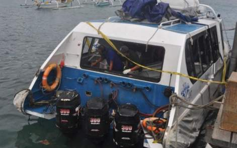 Police investigators examine the Gili Cat 2 boat following an explosion while it was enroute to nearby island of Lombok