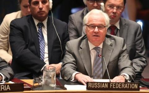 Three men in suits, including Vitaly Churkin the Russian ambassador to the United Nations, sit behind a desk sign reading Russian Federation at the UN Security Council in New York