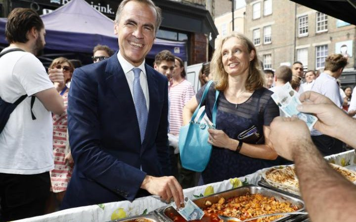 Bank of England Governor Mark Carney (left) dips a new plastic £5 note into a tray of food