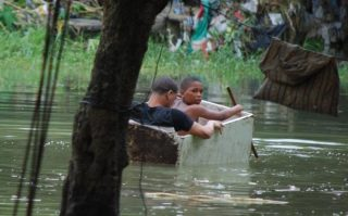 Two boys float in an old wooden box in an area flooded by heavy rains caused by Hurricane Matthew, in Santo Domingo, Dominican Republic