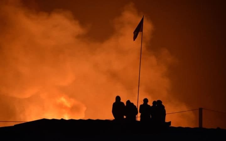 """People look at smoke rising during the demolition of the Calais """"Jungle"""" camp"""