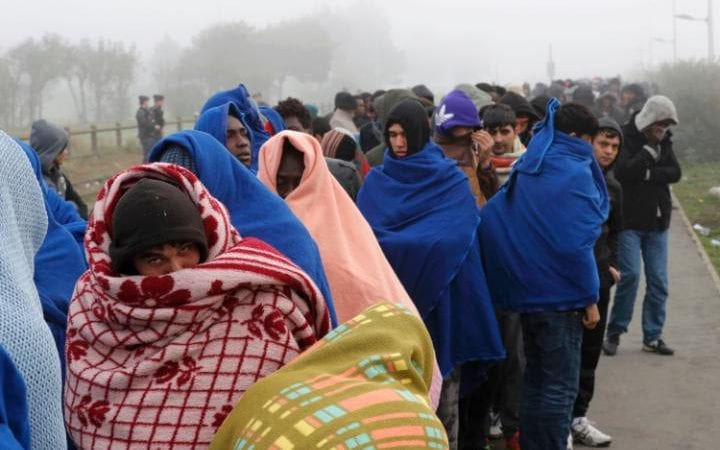 Migrants queue on the third day of their evacuation and transfer to reception centers in France