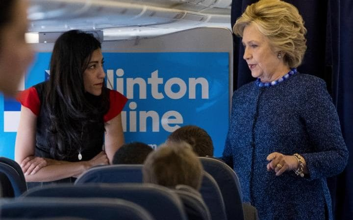 Democratic presidential candidate Hillary Clinton speaks with senior aide Huma Abedin aboard her campaign plane at Westchester County Airport