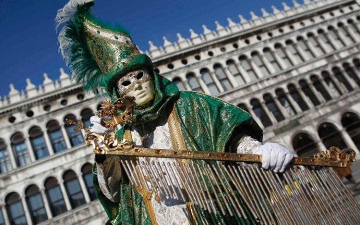 A masked reveller poses in St Mark's Square during Carnival celebrations in Venice. Surveys suggest two-thirds of locals still speak local dialects, as well as Italian.