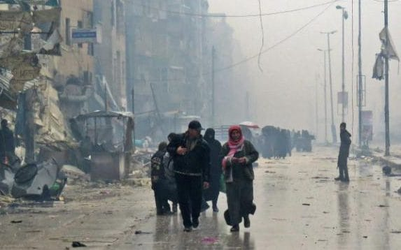 A stream of civilians walk down a devastated and foggy street in the Bustan al-Qasr neighbourhood of Aleppo
