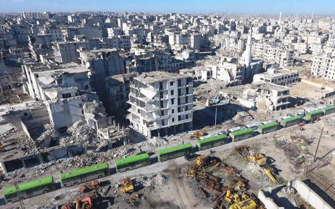 A convoy of uses and ambulances wait at a crossing point at Amiriyah District of Aleppo, Syria on December 15