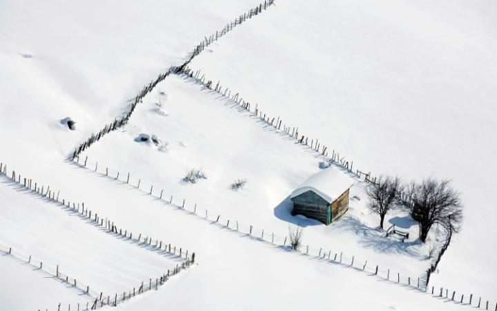 a wooden cottage is covered in snow in the Talesh mountains, close to the Caspian Sea