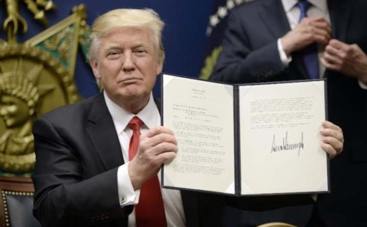 Donald Trump holds up Executive Orders he signed in the Pentagon on January 27, 2017.