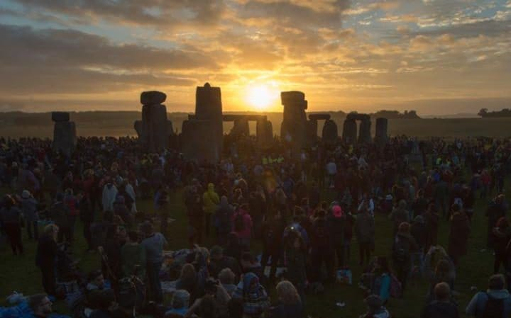 Summer solstice at Stonehenge, with the sun rising in the distance.