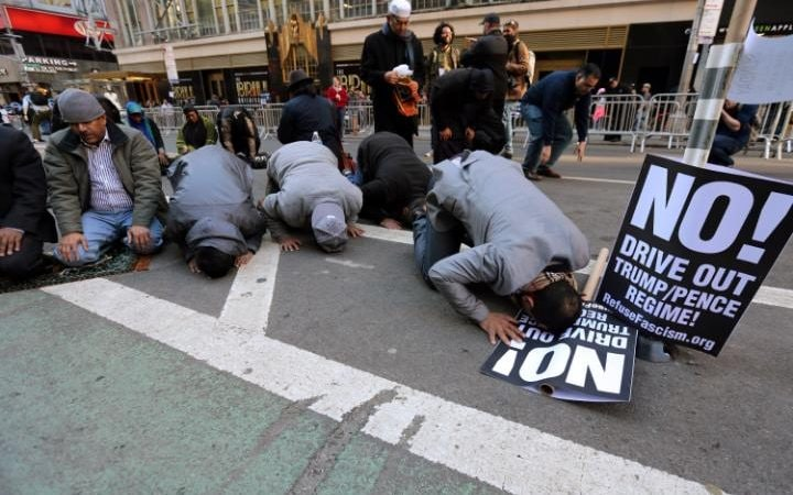 Muslim men kneel on Broadway Ave. as they take part in afternoon prayers during an