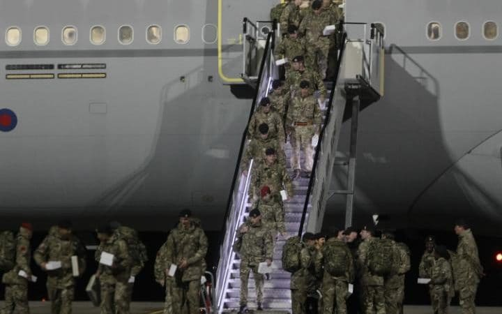 British soldiers leave the plane after arriving at the Amari Air Base