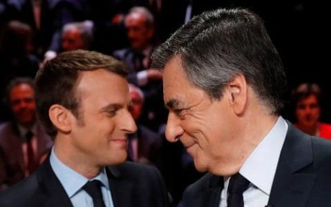 Emmanuel Macron, left, greets Francois Fillon ahead of the televised debate