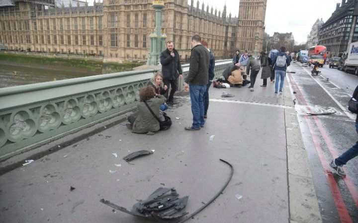 Injured victims are seen on Westminster Bridge this afternoon, with wreckage strewn across the pavement.