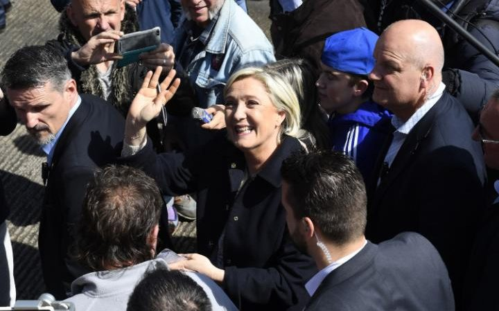 Marine Le Pen greets people during her visit to the harbour in Erquy, western France on March 31