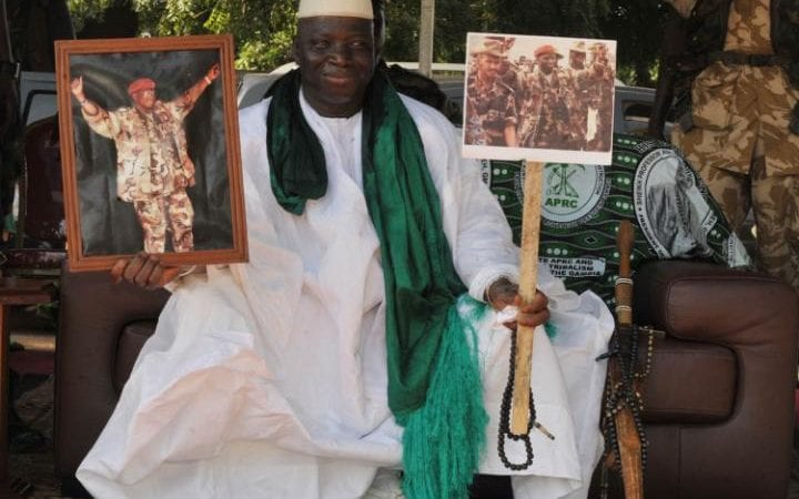 Yahya Jammeh poses with pictures of himself in military outfits in 2011