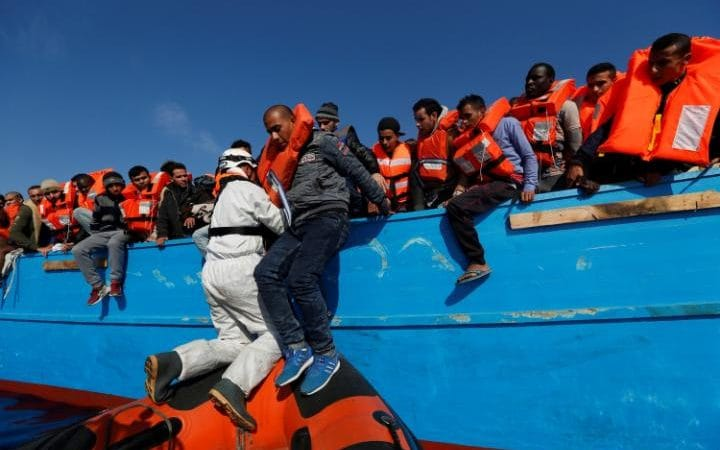 Migrants on a wooden boat are rescued by the Malta-based NGO Migrant Offshore Aid Station (MOAS) in the central Mediterranean