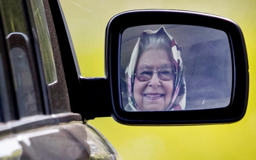 The Queen grins as she drives through the grounds of Windsor Castle in her Range Rover