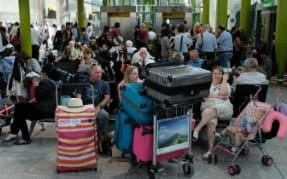 Travellers wait stranded at Heathrow Airport Terminal 5 after British Airways cancelled its flights