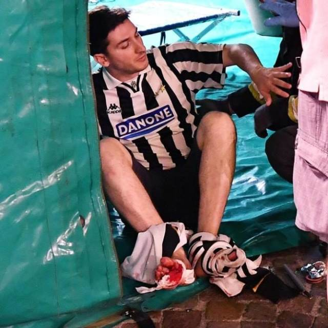 An injured Juventus fan lies in San Carlo's square at the end of the Champions League final