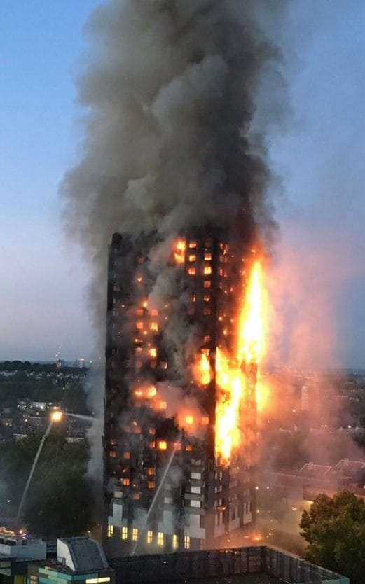 Thick smoke billows from Grenfell Tower as the fire rages in the early hours