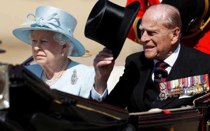 Queen Elizabeth II and Prince Philip, Duke of Edinburgh, travel in the royal carriage during the annual Trooping the Colour parade