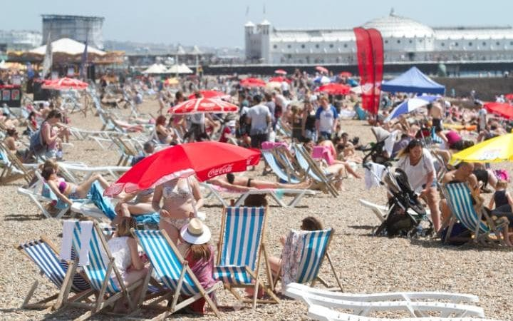 Large crowds of sun seekers pack Brighton beach to cool off on scorching day