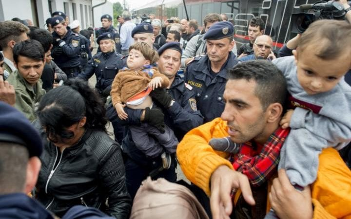 """Austrian policemen and migrants in the Austrian village of Nickelsdorf on September 5, 2015. Thousands of migrants streamed into Austria from Hungary, in what Vienna called a """"wake up call"""" for Europe to get to grips with its biggest refugee influx since World War II."""