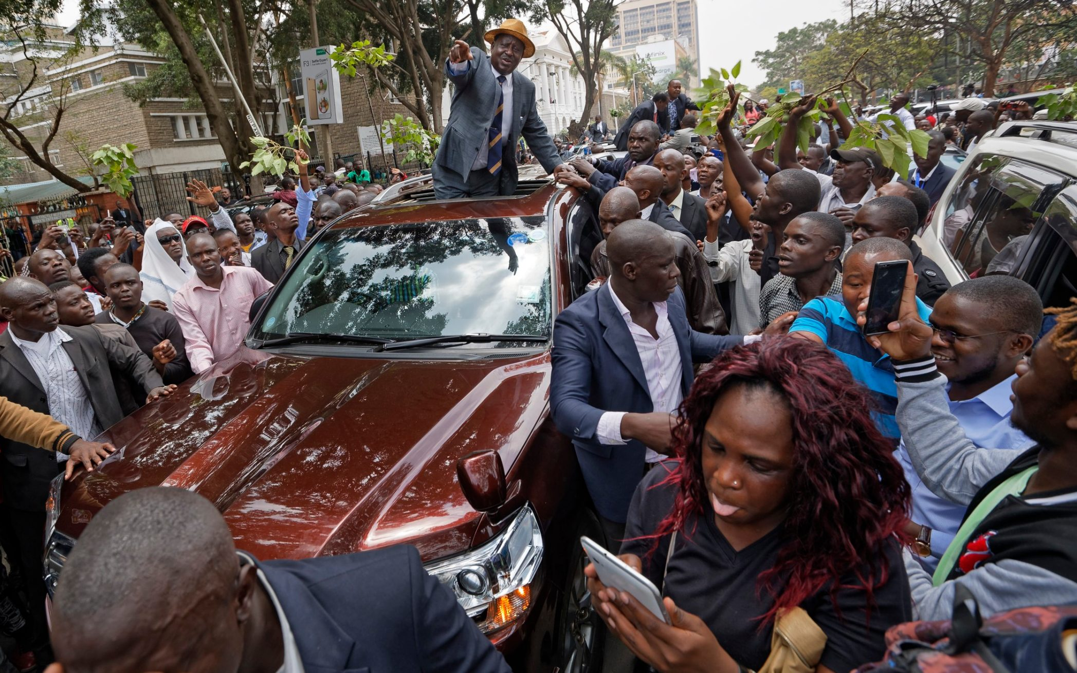 Opposition leader Raila Odinga smiles and waves to a crowd of his supporters as he leaves the Supreme Court in downtown Nairobi