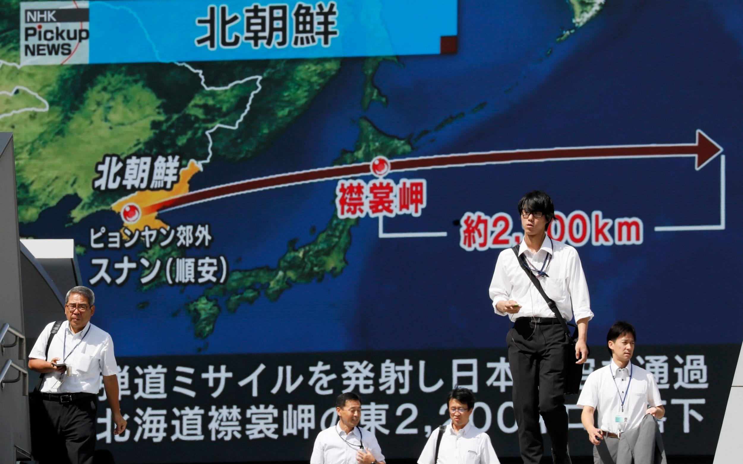 Pedestrians walk under a large-scale monitor displaying the flying course of a North Korean ballistic missile flying over Japan