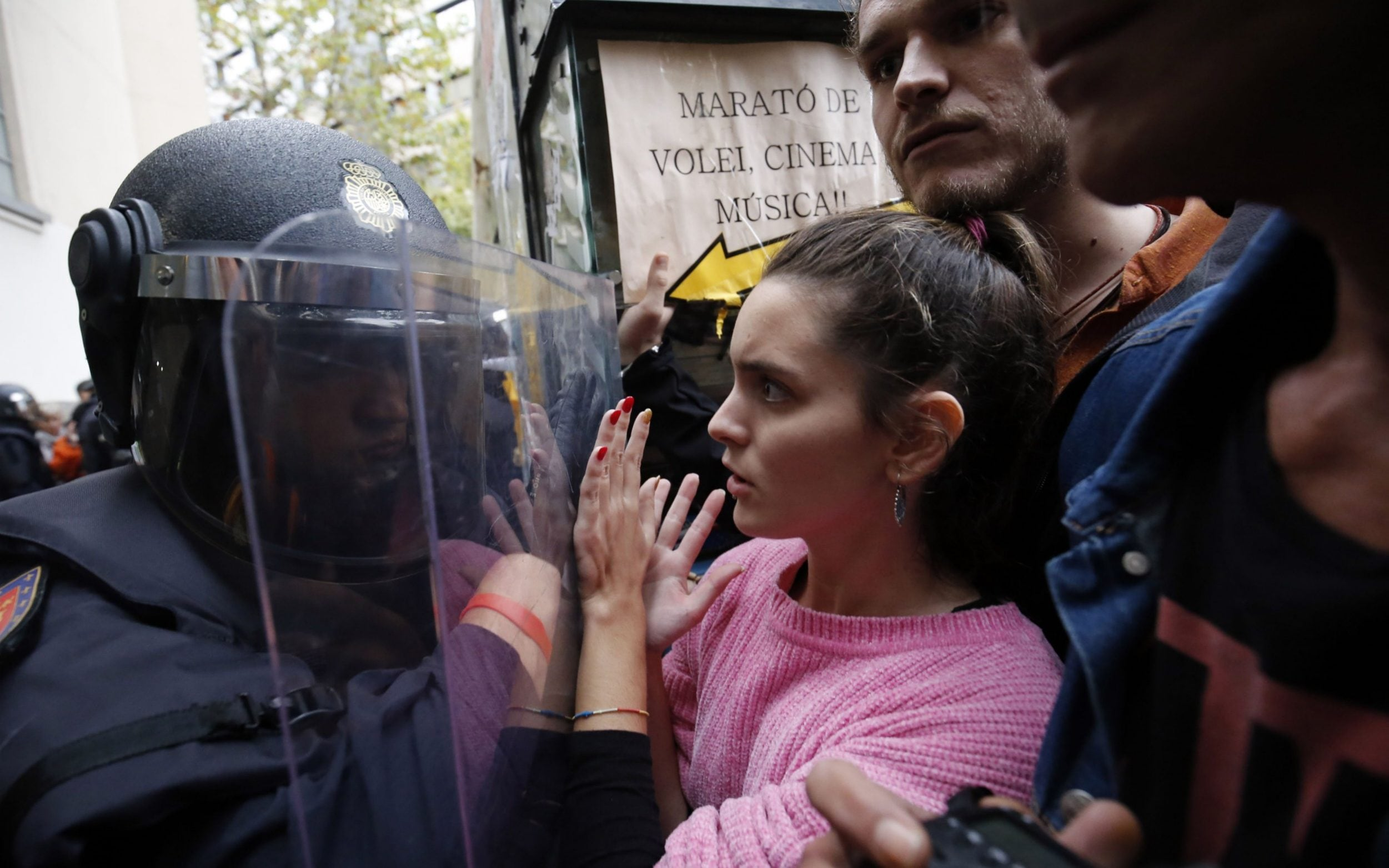 Spanish police push people with a shield outside a polling station in Barcelona