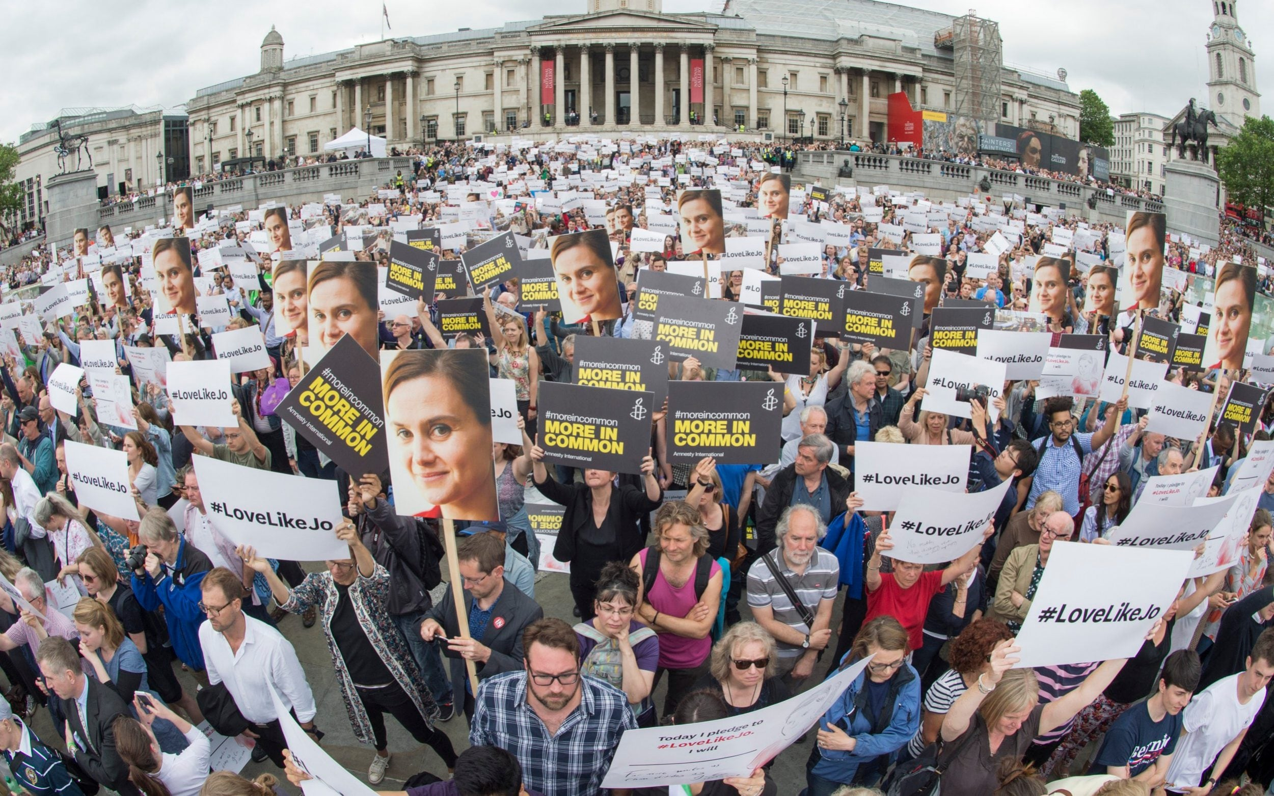 A huge crowd of people hold placards with photographs of the murdered MP Jo Cox and others saying '#LoveLikeJo'