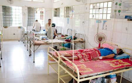 A patient lies on a bed in a hospital ward