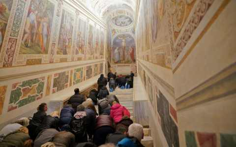 Catholic faithful clamber up the Holy Staircase on their knees after its restoration