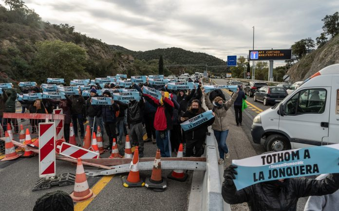 Protesters hold banners as they crowd onto the highway