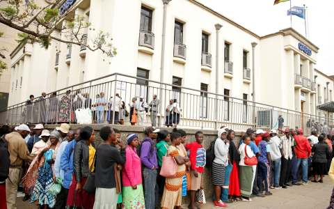 People queue to withdraw money in Harare after Zimbabwe introduced a new currency