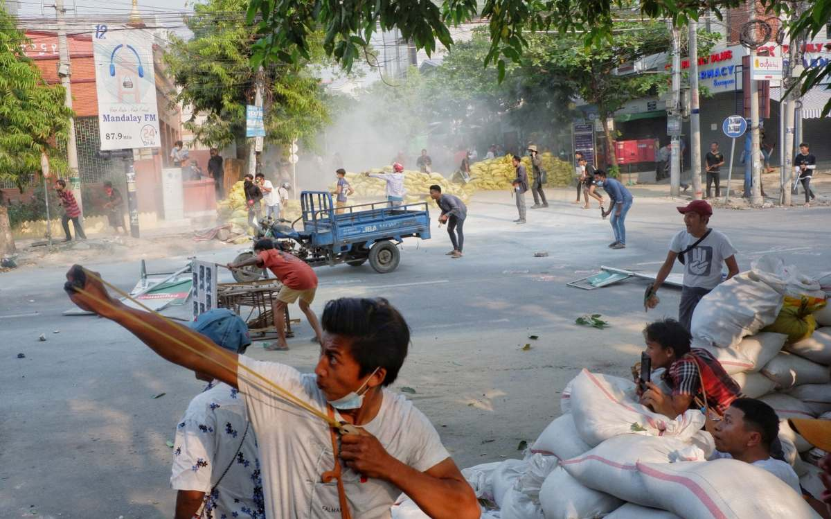 A man uses a slingshot during the security force crack down on anti-coup protesters in Mandalay