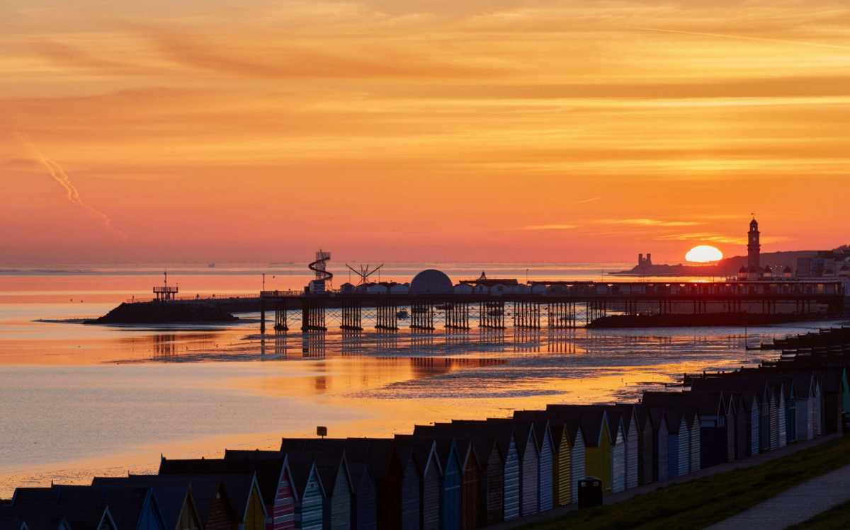 Sunrise between Reculver towers and the clock tower at Herne Bay with the pier and harbour