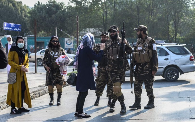 Members of the Taliban special forces stop a woman protestor from continuing a demonstration