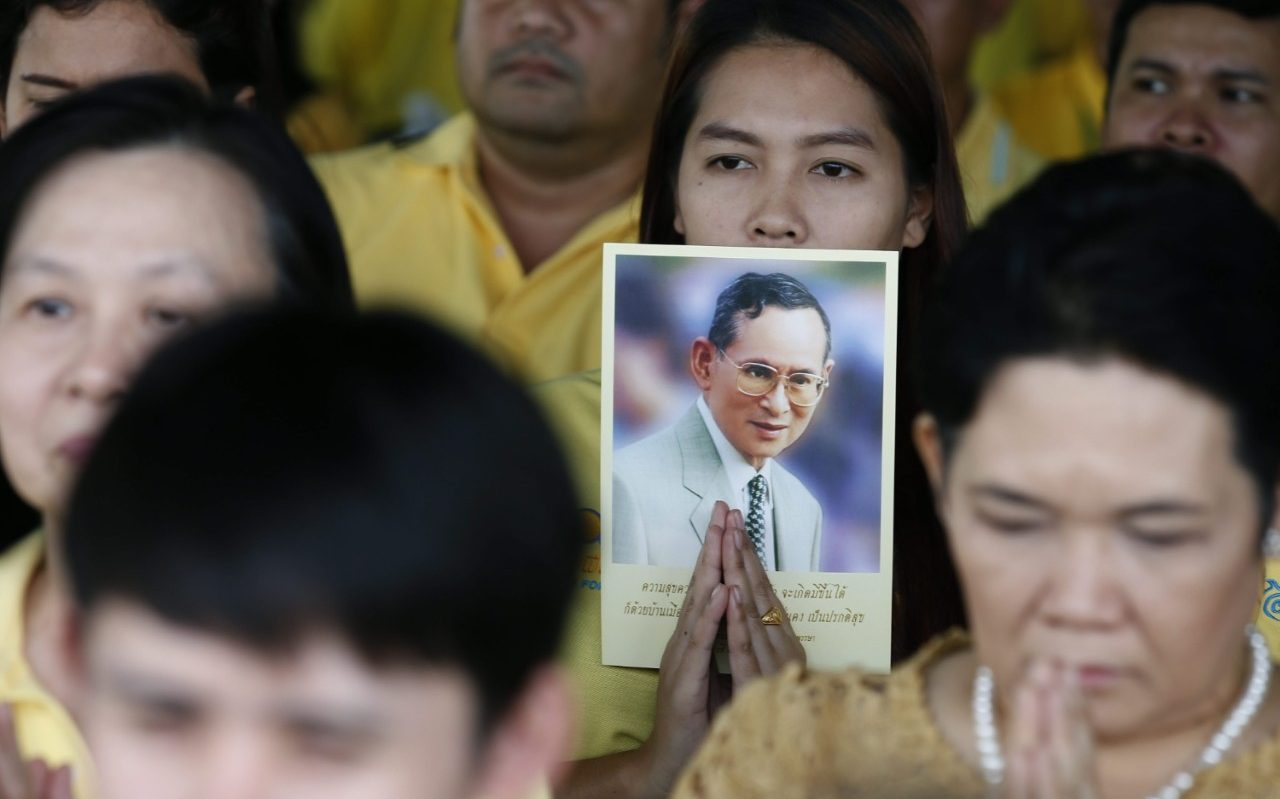 Thai people wearing yellow shirts, the color of the king, hold pictures of Thai King Bhumibol Adulyadej as they pray during the celebrations of the monarch's 70th anniversary