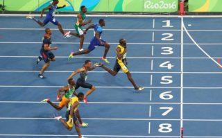 Usain Bolt starts celebrating as he crosses the finish line