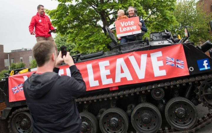 """Jaime Gray uses a smartphone to take a photograph of his 13-month-old son Robert with a """"Vote Leave"""" placard on a FV432 modified armored personnel carrier, in the Southwick district of Sunderland, U.K., on Saturday, June 4, 2016."""
