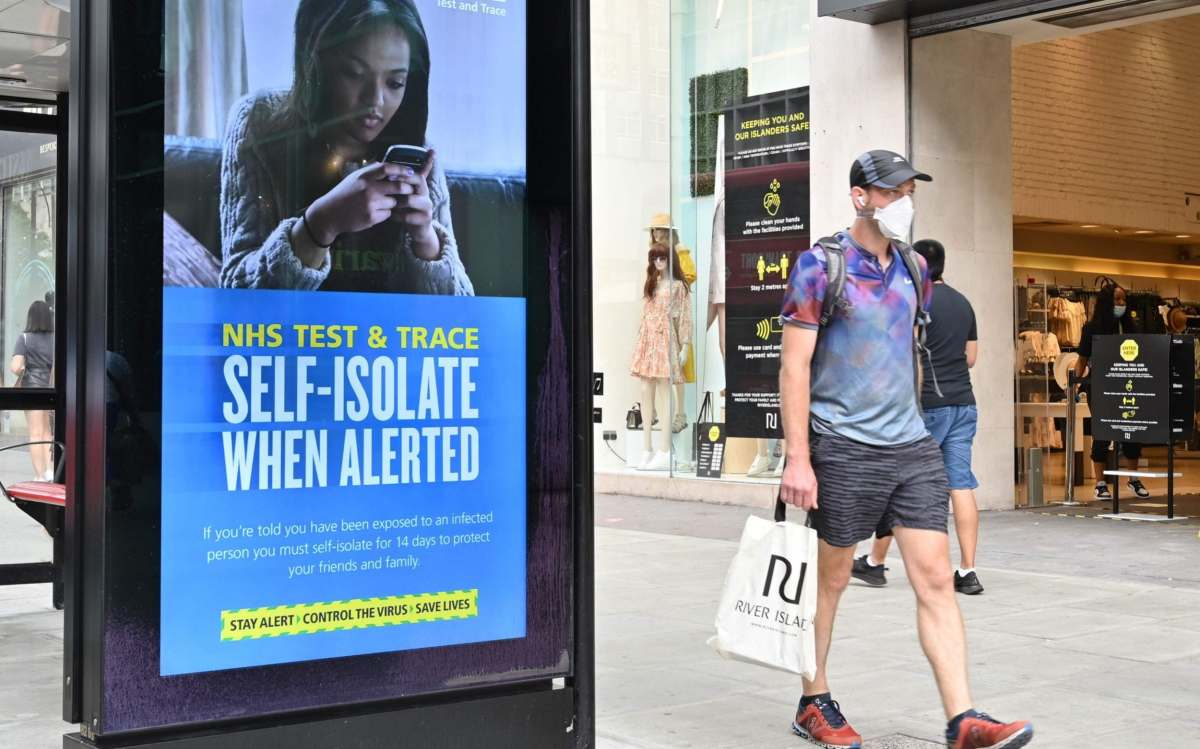 A shopper walks past an advertisment for the UK government's NHS Test and Trace system in Regent Street in London