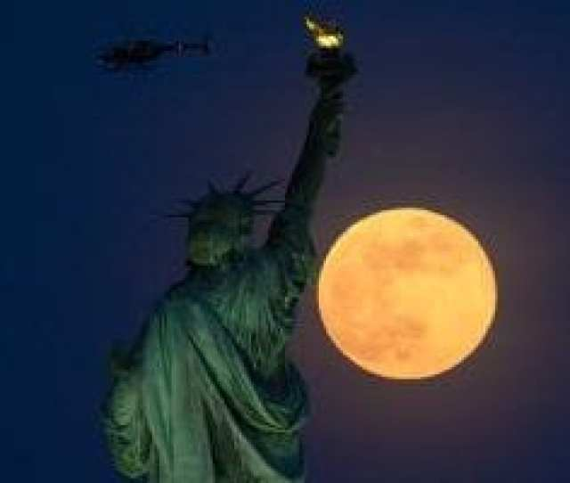 A Helicopter Flies Past As The Full Moon Rises Behind The Statue Of Liberty On May