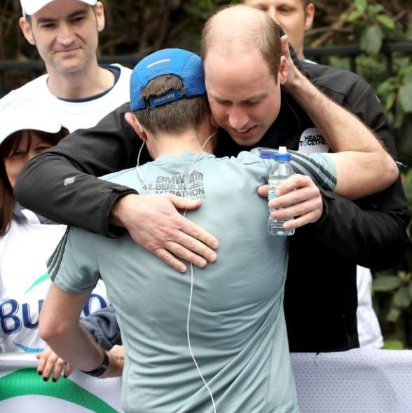 The Duke of Cambridge hugs a runner as he hands out water
