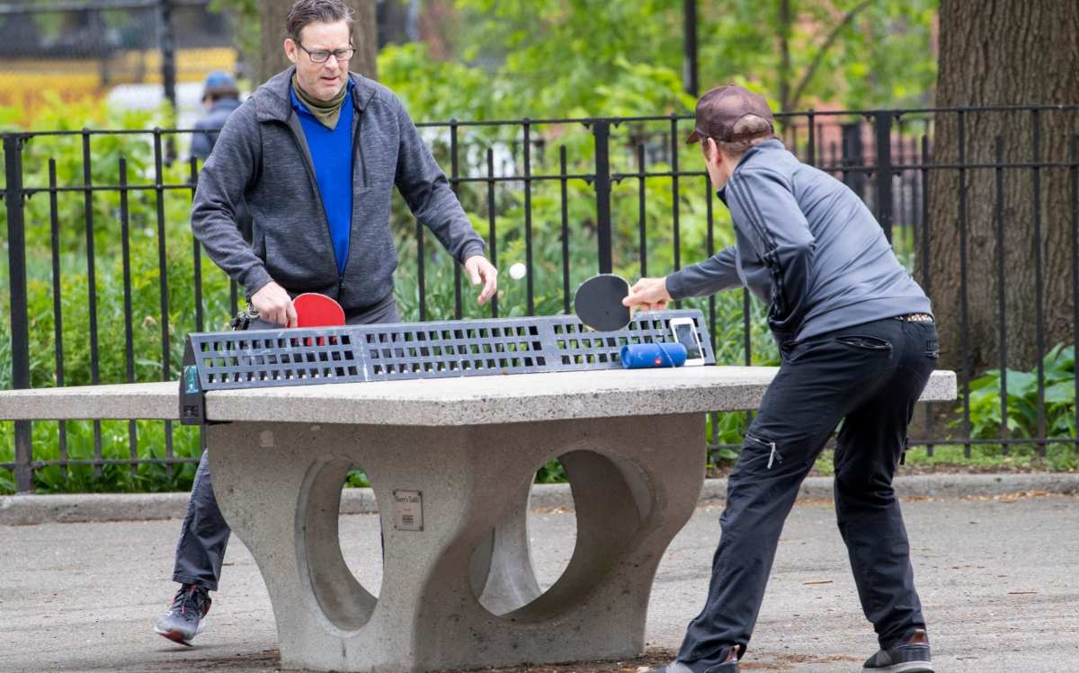 In this Monday, May 11, 2020 photo, men play ping pong without face masks at Tompkins Square Park in New York. New York's governor has ordered masks for anyone out in public who can't stay at least six feet away from other people. Yet, while the rule is clear, New Yorkers have adopted their own interpretation of exactly when masks are required, especially outdoors