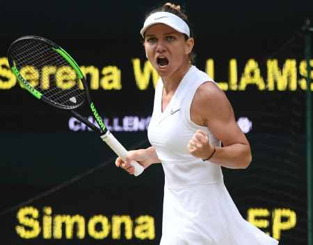 omania's Simona Halep celebrates breaking the serve of US player Serena Williams in the second set during their women's singles final on day twelve of the 2019 Wimbledon Championships